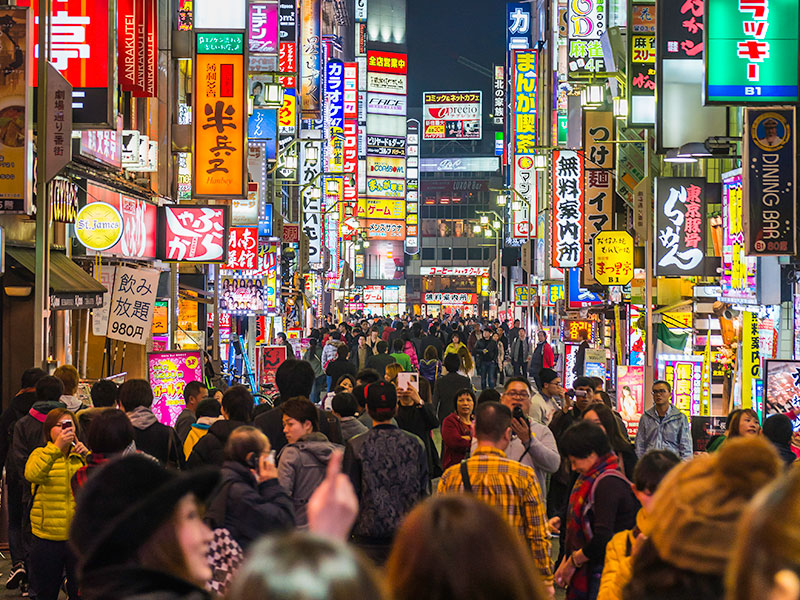 Tokyo nightlife crowded streets and colourful neon shopping signs Japan