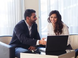 Young business couple meeting with tech devices