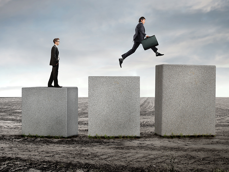 Businessmen on stone cubes jumping towards higher ones