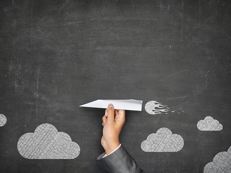 Businessman hand holding paper plane on front of vintage full frame black blank blackboard no frame and couple clouds