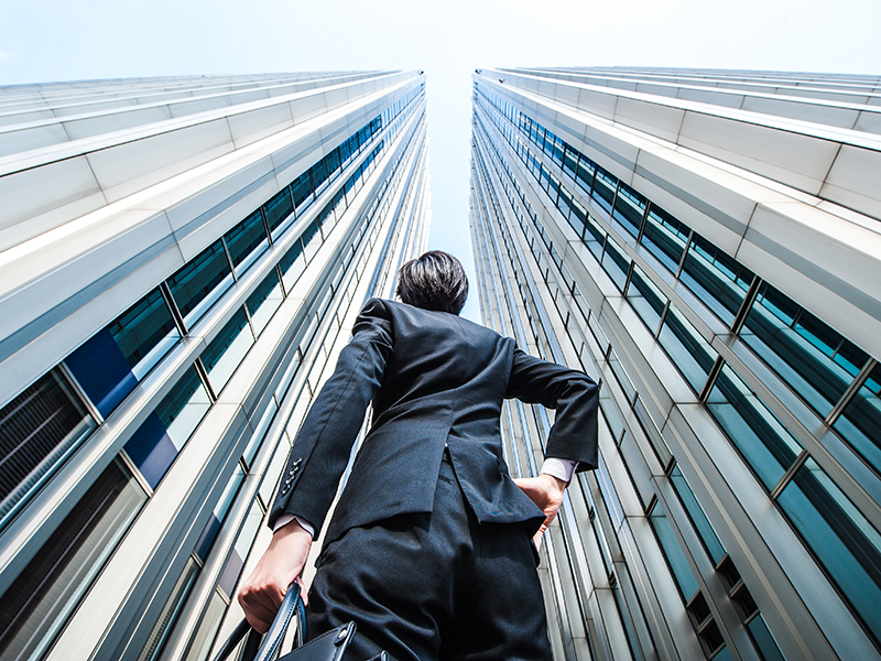 Businessman looking up at the high building, low angle