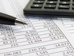 A calculator and pen on financial papers