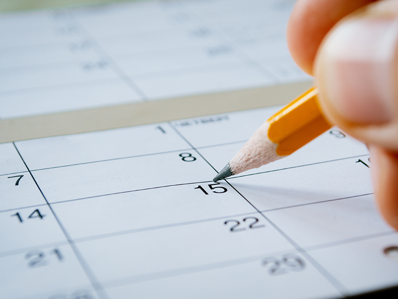 Person marking the date of the 15th with a pencil on a blank calendar with date squares as a reminder of an important day or to schedule a meeting or event