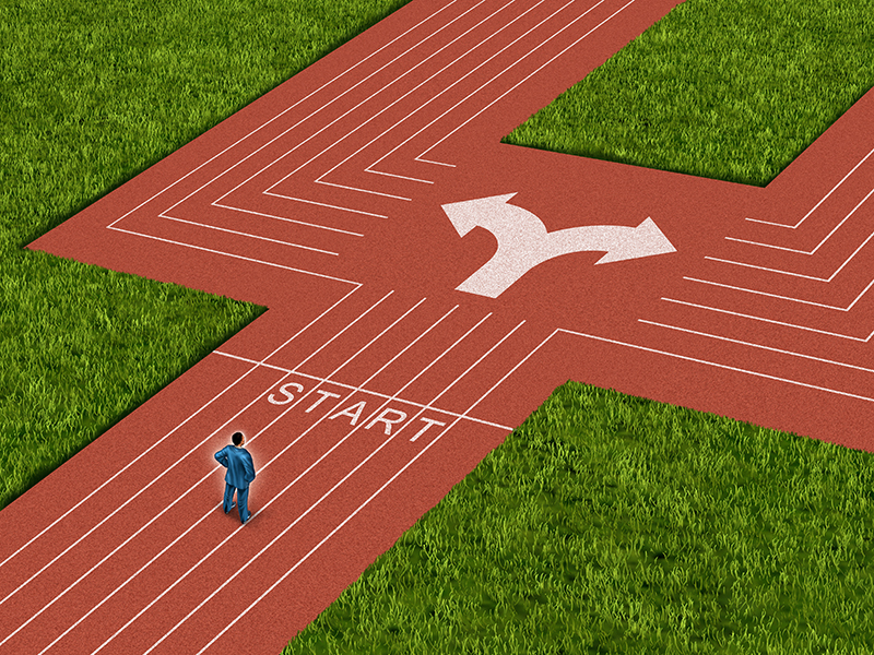 Businessman crossroads concept choosing the right path as a man on a track and field sport track facing a difficult choice and dilemma with two different business directions as a metaphor for decision crisis