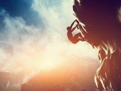 A silhouette of man climbing on rock, mountain at sunset Adrenaline, strenght, ambition