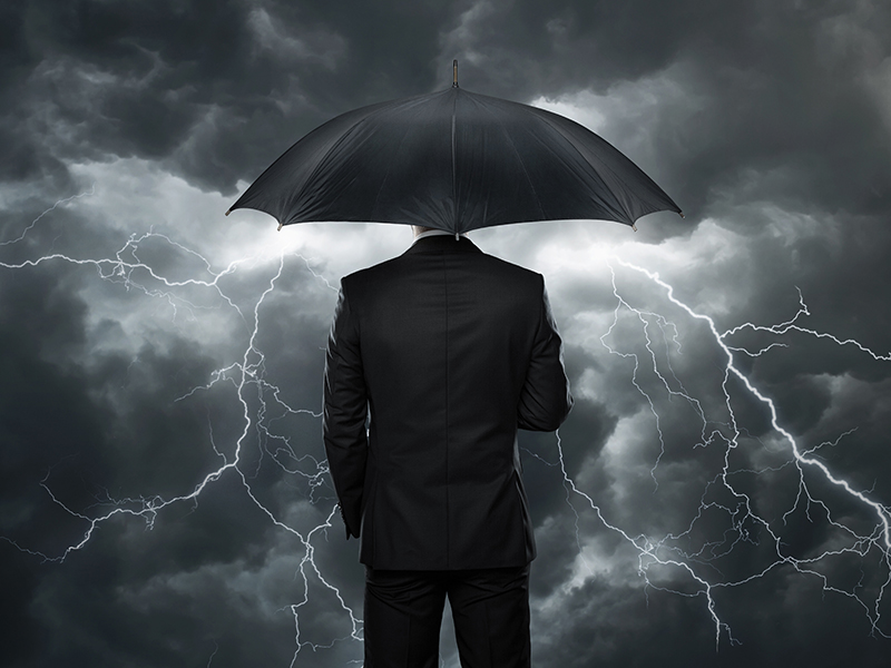 Trouble ahead, Businessman with umbrella standing in front of stormy clouds