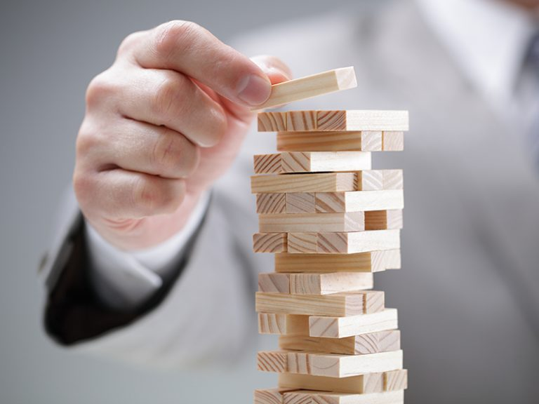 Planning, risk and strategy in business, businessman gambling placing wooden block on a tower