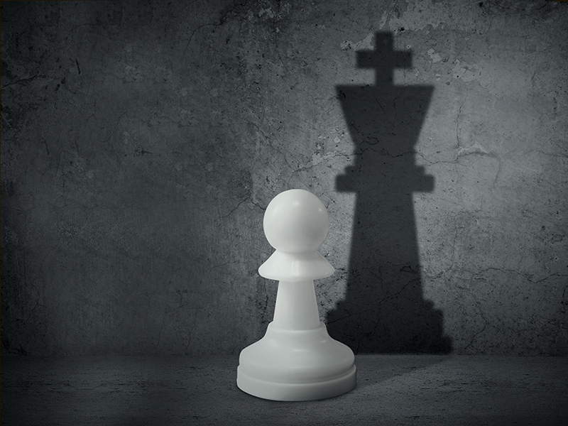 White chess pawn with the shadow of a king