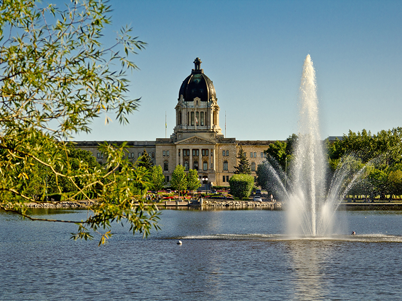 The Saskatchewan Legistlative building in the background and a fountain on Wascana lake on a lovely summer day in Regina.
