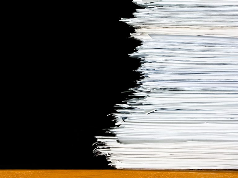 stack of documents or files, overload of paperwork on black background