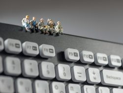 Miniature workers sitting on top of keyboard. Technology concept. Macro photo