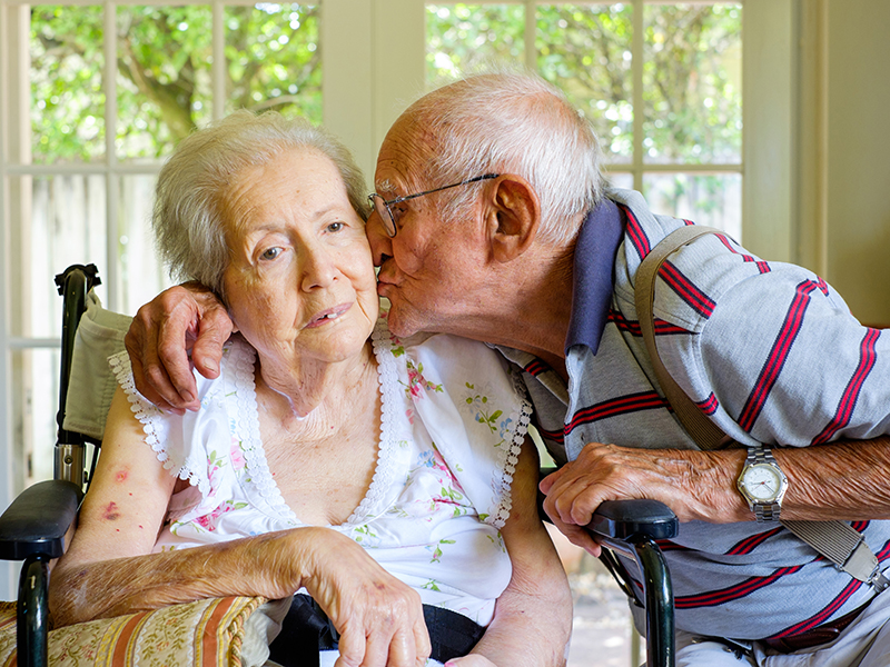 Elderly eighty plus year old woman in a wheel chair in a home setting with her husband