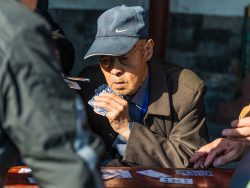 Beijing, China - October 15, 2013: Portrait of a Elderly Chinese men enjoying a game of cards with friends in the surroundings of the Temple of Heaven in Beijing, China.