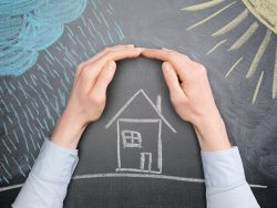 A young businesswoman protects a house from the elements - rain or storm and sun. Blackboard drawing, top view.