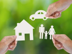 Hand holding a paper home, car, family on green background, insurance concept