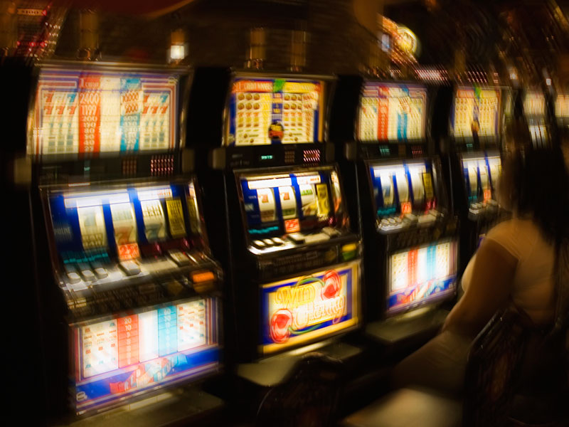 People in casino, looking at slot machine