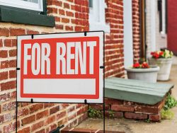 Red For Rent sign closeup against brick building