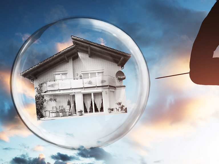 Human Hand Poking House And Bubble With Needle Against Cloudy Sky