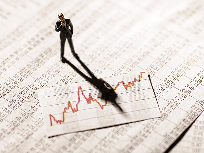 Model figure stands on rate tables and looks skeptically on a graph with stock prices.