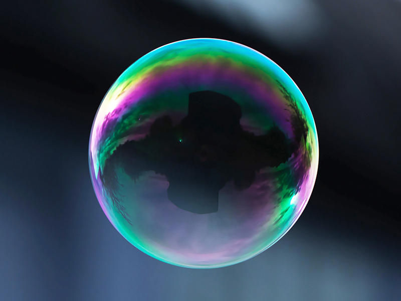 A flying soap bubble with reflection of a building.