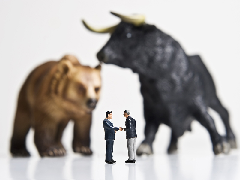 Business figurines placed with bull and bear figurines.