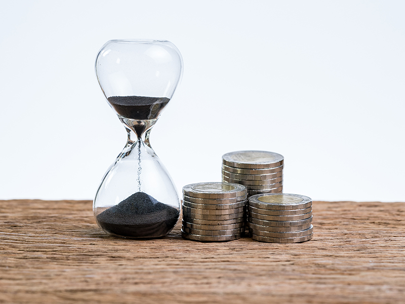 Financial or investment time counting with hourglass or sandglass and stack of coins on wooden table with white background.