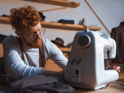 Focused young fashion designer in eyeglasses working with sewing machine