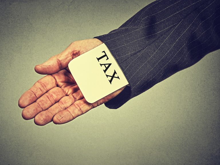 Corruption illegal criminal activity tax evasion economy ponzi scheme concept. Closeup man hand hiding tax card in a sleeve of a suit isolated on gray wall background