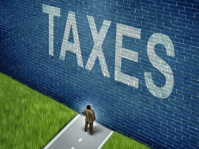 Tax problems business and financial concept as a businessman on a road to success blocked by a brick wall with the word taxes painted on the surface as a metaphor for finance issues as an adversity to growth.