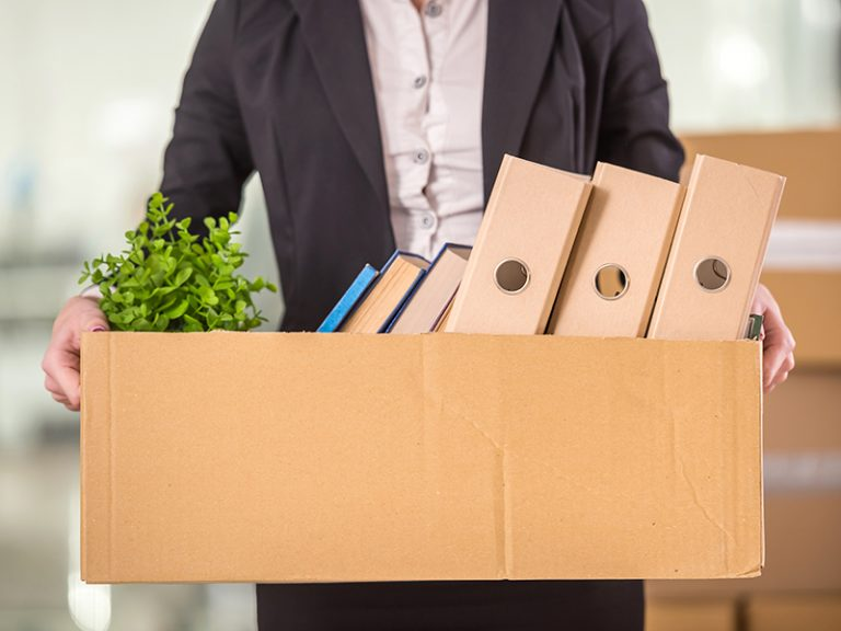 Close-up. Smiling young businesswoman holding cardboard box with her things.