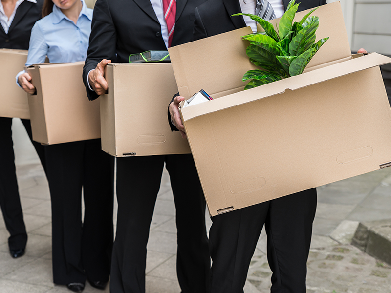 Close-up Of Unemployed Businesspeople Carrying Cardboard Boxes