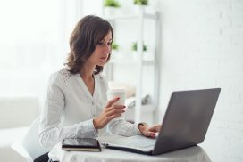 Young business woman working at desk typing on a laptop in office and drinking coffee.