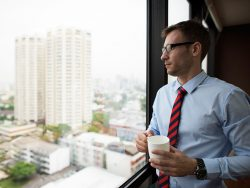 Businessman Holding coffee thinking