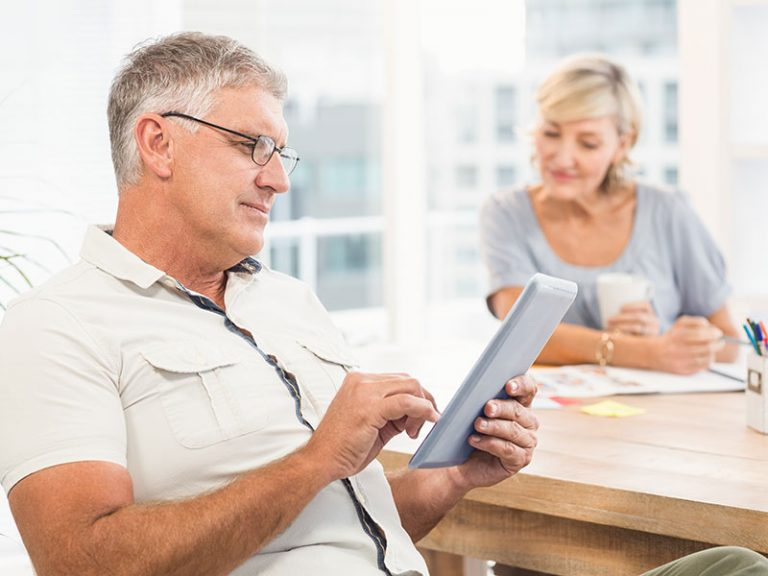 Side view of a serious businessman scrolling on a tablet