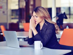 Young business woman suffering stress working at office computer