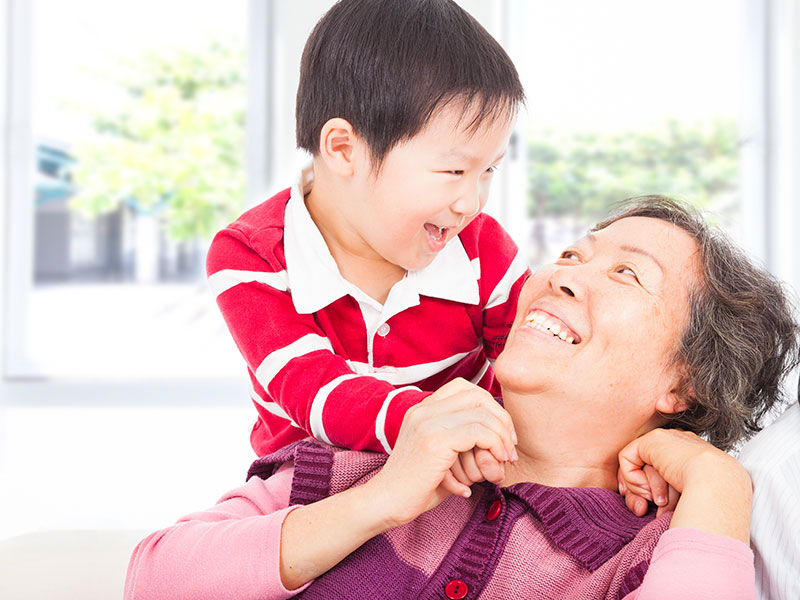 Stock Photo - a boy playing with grandmother at home