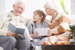 Grandfather reading the book next to grandson with tablet