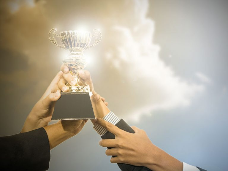 Business people holding trophy award after win competitor.
