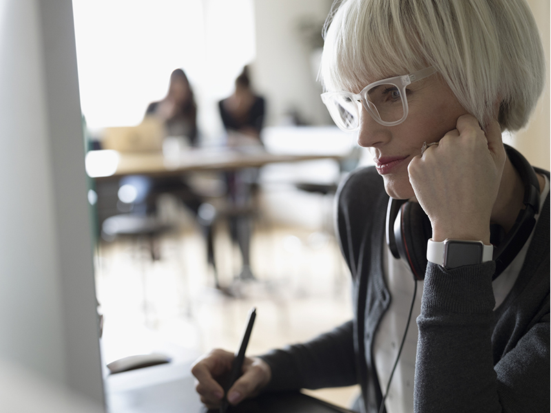 Focused female graphic designer using graphics tablet at computer