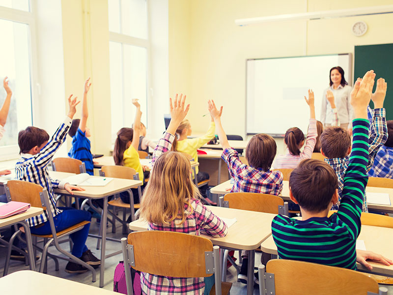 group of school kids with teacher sitting in classroom and raising hands