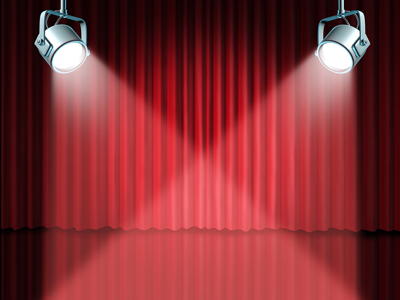 11119737 - in the spotlight featuring concept for the theater stage with glowing lights on red velvet cinema curtain and drapes representing the entertainment communications concept of an important announcement in a rich cinema and theatrical environment.