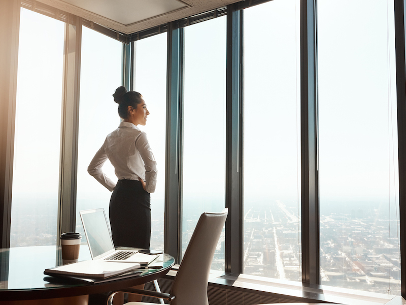Rearview shot of an attractive young businesswoman standing with her hands on her hips in the office