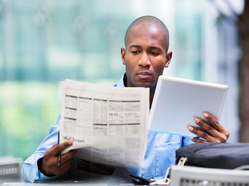 man checking stocks on newspaper and tablet