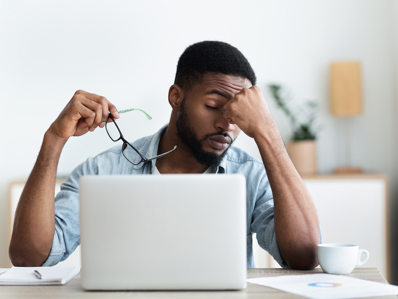 Tired african american employee having headache after working on laptop in office, copy space