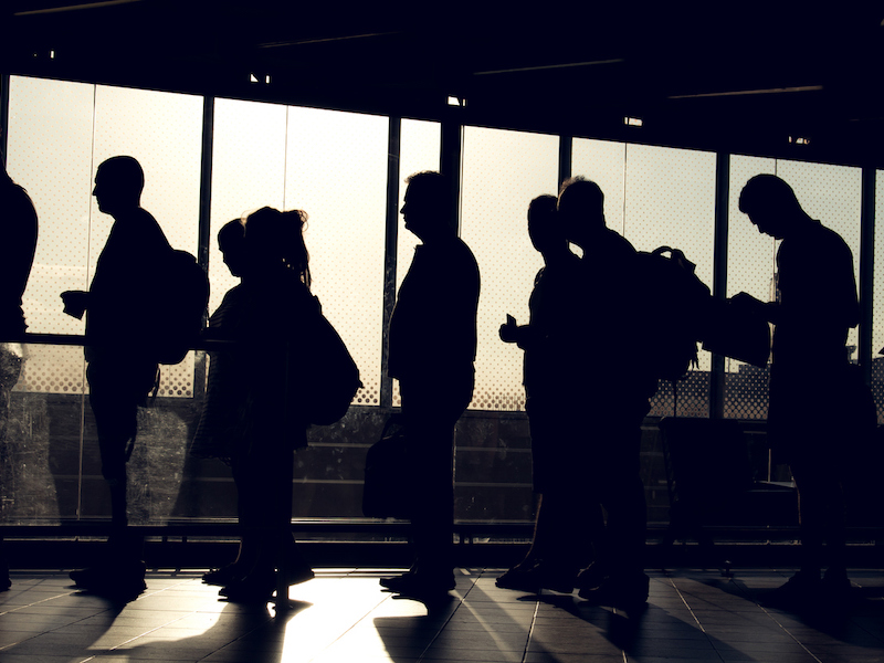 people are waiting in the aterminal with their silhouette reverse lighted image