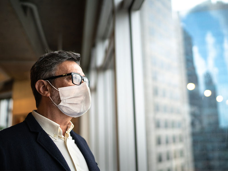 Mature businessman looking out of window with face mask stock photo