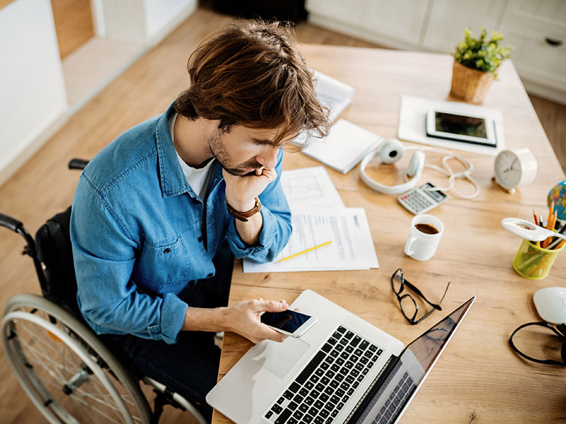 young man in wheelchair working on laptop