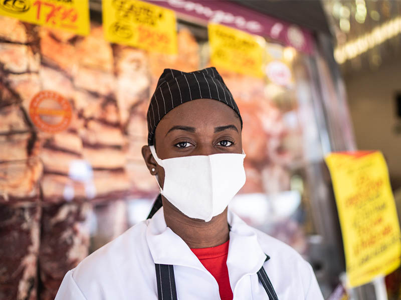 Portrait of female butcher working at butcher's shop - with face mask